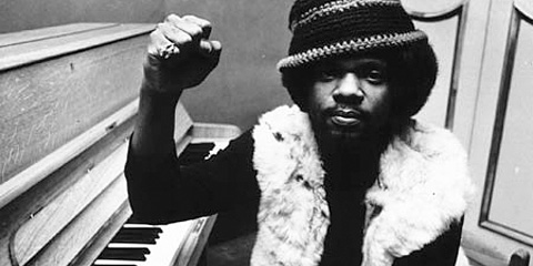 Photo of BIlly Preston at a piano with his right fist raised in a clench